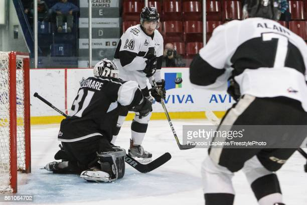Mathieu Bellemare of the Gatineau Olympiques makes a save as Joel Teasdale of the BlainvilleBoisbriand Armada keeps his eyes on the rebound on...