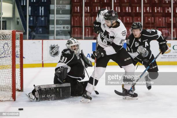 Mathieu Bellemare of the Gatineau Olympiques makes a save as Will Thompson defends against Thomas Ethier of the BlainvilleBoisbriand Armada on...