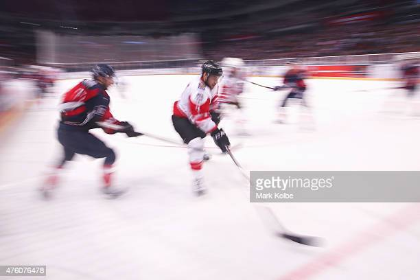 Mathieu Brisebois of Canada skates up the ice with the puck during the 2015 Ice Hockey Classic match between the Unites States and Canada at...