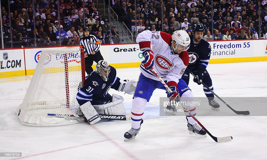 <a gi-track='captionPersonalityLinkClicked' href=/galleries/search?phrase=Mathieu+Darche&family=editorial&specificpeople=2112288 ng-click='$event.stopPropagation()'>Mathieu Darche</a> #52 of the Montreal Canadiens plays the puck as goaltender Ondrej Pavelec #31 and Mark Stuart #5 of the Winnipeg Jets defend the net during third period action at the MTS Centre on December 22, 2011 in Winnipeg, Manitoba, Canada.