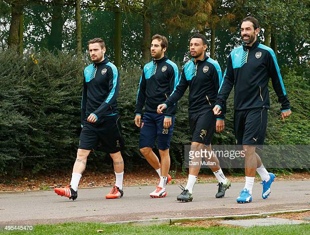 Mathieu Debuchy Mathieu Flamini Francis Coquelin and exArsenal player Robert Pires walk to the pitch during an Arsenal training session on the eve of...