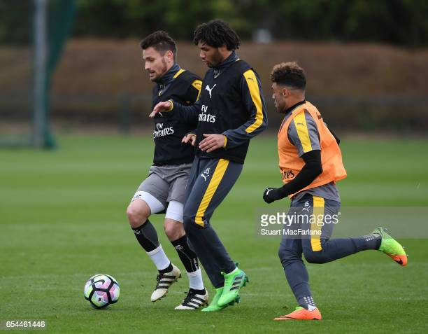 Mathieu Debuchy Mohamed Eleney and Alex OxladeChamberlain of Arsenal during a training session at London Colney on March 17 2017 in St Albans England