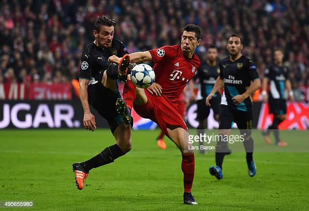 Mathieu Debuchy of Arsenal and Robert Lewandowski of Bayern Muenchen compete for the ball during the UEFA Champions League Group F match between FC...