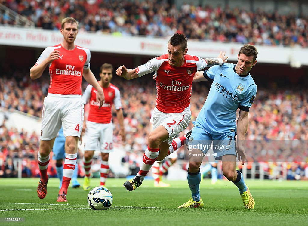 Mathieu Debuchy of Arsenal is challenged by James Milner of Manchester City during the Barclays Premier League match between Arsenal and Manchester...