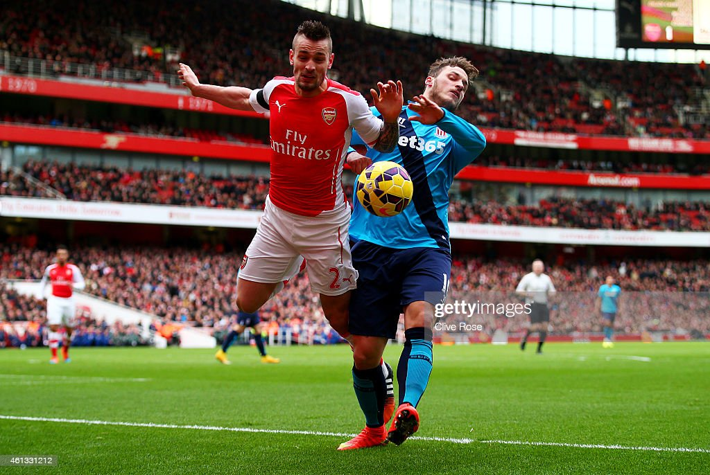 Mathieu Debuchy of Arsenal is challenged by Marko Arnautovic of Stoke City and subsequently picks up an injury during the Barclays Premier League match between Arsenal and Stoke City at Emirates Stadium on January 11, 2015 in London, England.