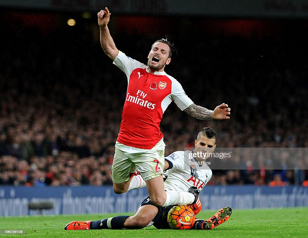 Mathieu Debuchy of Arsenal is fouled by Erik Lamela of Tottenham during the Barclays Premier League match between Arsenal and Tottenham Hotspur at...