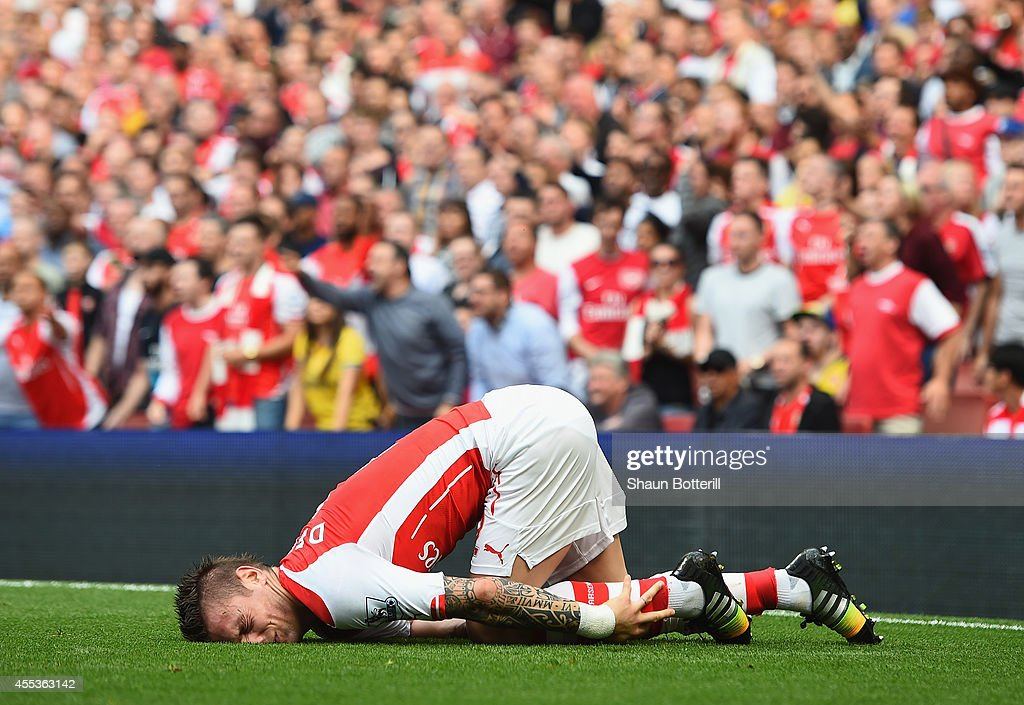 Mathieu Debuchy of Arsenal is injured in the first half during the Barclays Premier League match between Arsenal and Manchester City at Emirates...