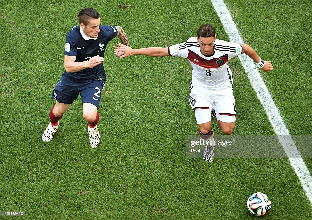 Mathieu Debuchy of France challenges Mesut Oezil of Germany during the 2014 FIFA World Cup Brazil Quarter Final match between France and Germany at...