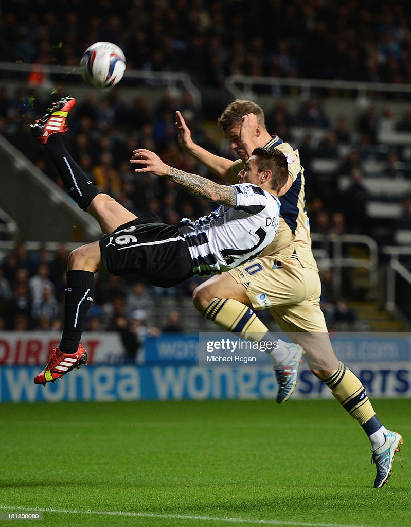 Mathieu Debuchy of Newcastle United clears the ball from Matt Smith of Leeds United during the Capital One Cup Third Round match between Newcastle United and Leeds United at St James' Park on September 25, 2013 in Newcastle upon Tyne, England.