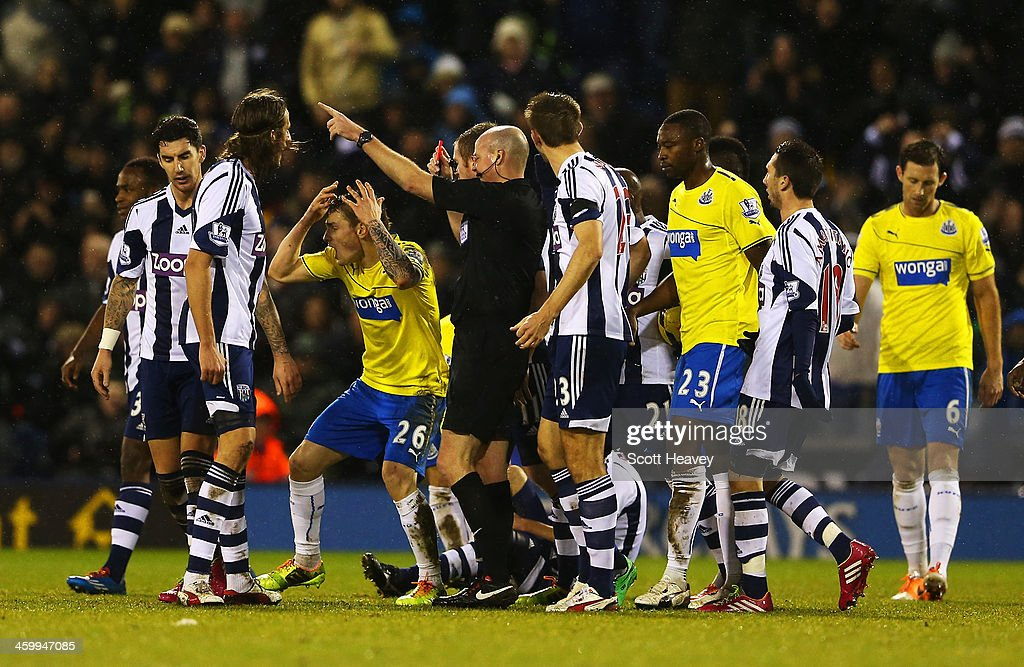 Mathieu Debuchy of Newcastle United is shown the red card by referee Lee Mason during the Barclays Premier League match between West Bromwich Albion...