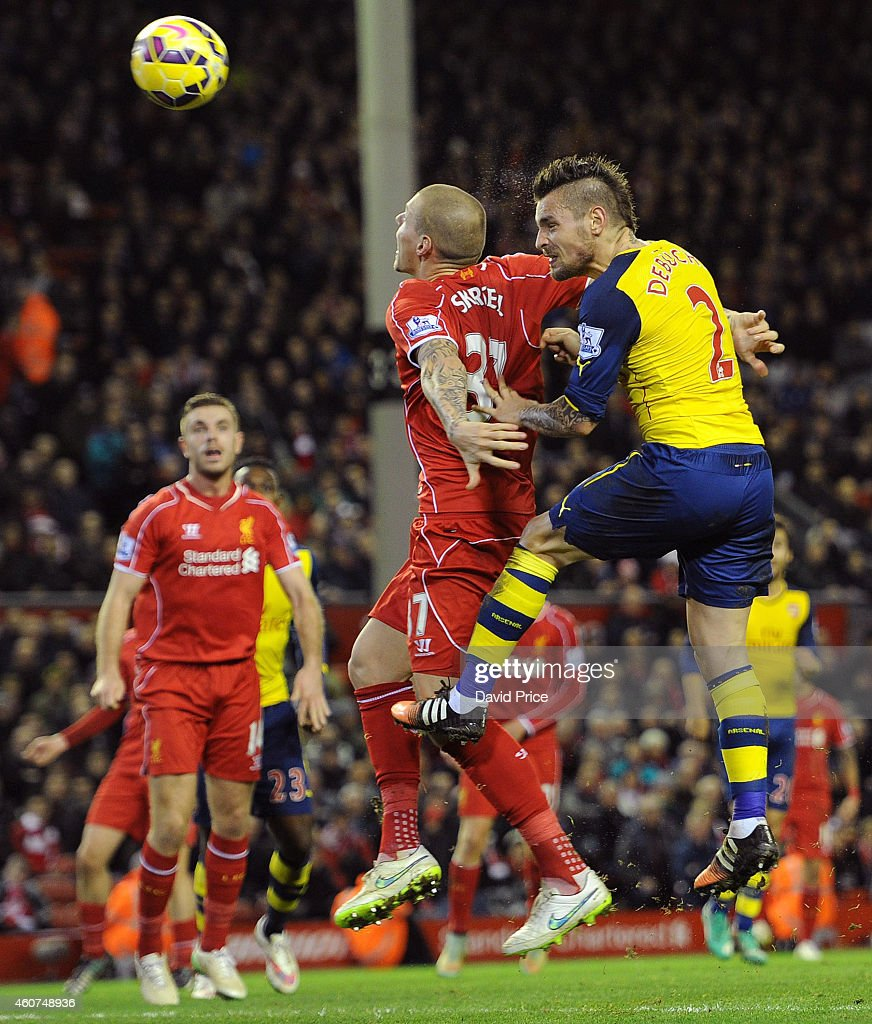 Mathieu Debuchy scores Arsenal's goal under pressure from Martin Skrtel of Liverpool during the match between Liverpool and Arsenal in the Barclays Premier League at Anfield on December 21, 2014 in Liverpool, England.