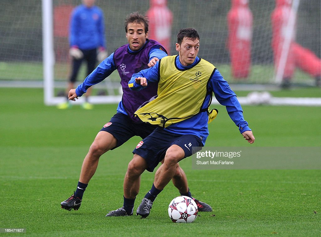 Mathieu Flamini and Mesut Oezil of Arsenal during a training session at London Colney on October 21, 2013 in St Albans, England.