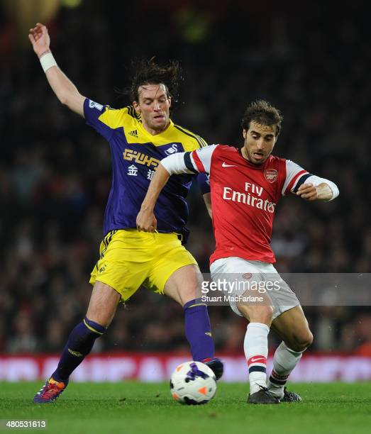 Mathieu Flamini of Arsenal challenged by Miguel Michu of Swansea during the Barclays Premier League match between Arsenal and Swansea City at...