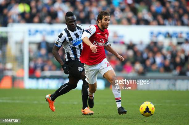 Mathieu Flamini of Arsenal is closed down by Cheick Tiote of Newcastle United during the Barclays Premier League match between Newcastle United and...