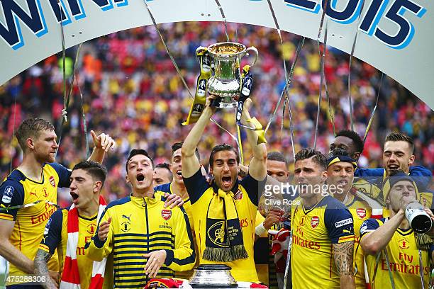 Mathieu Flamini of Arsenal lifts the trophy in celebration with team mates after the FA Cup Final between Aston Villa and Arsenal at Wembley Stadium...