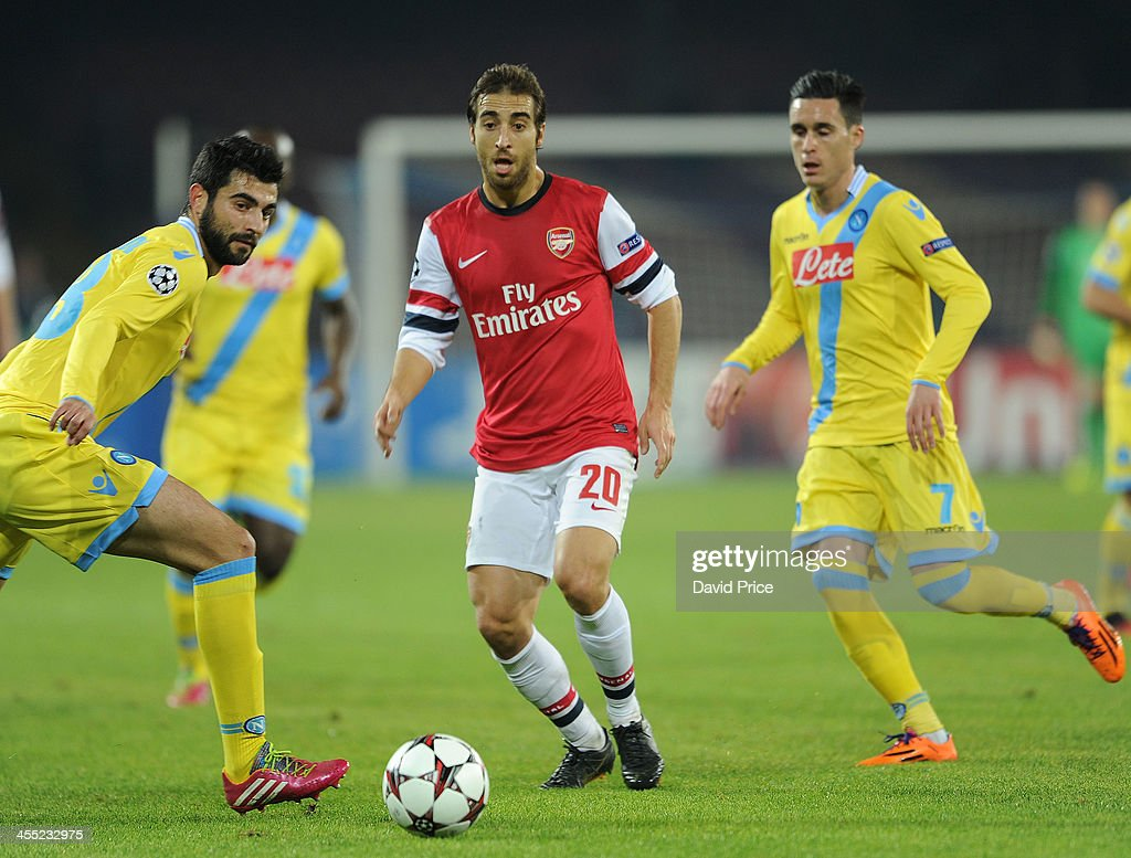 Mathieu Flamini of Arsenal passes the ball between Raul Albiol and Jose Cllejon of Napoli during the match Napoli against Arsenal in the UEFA...