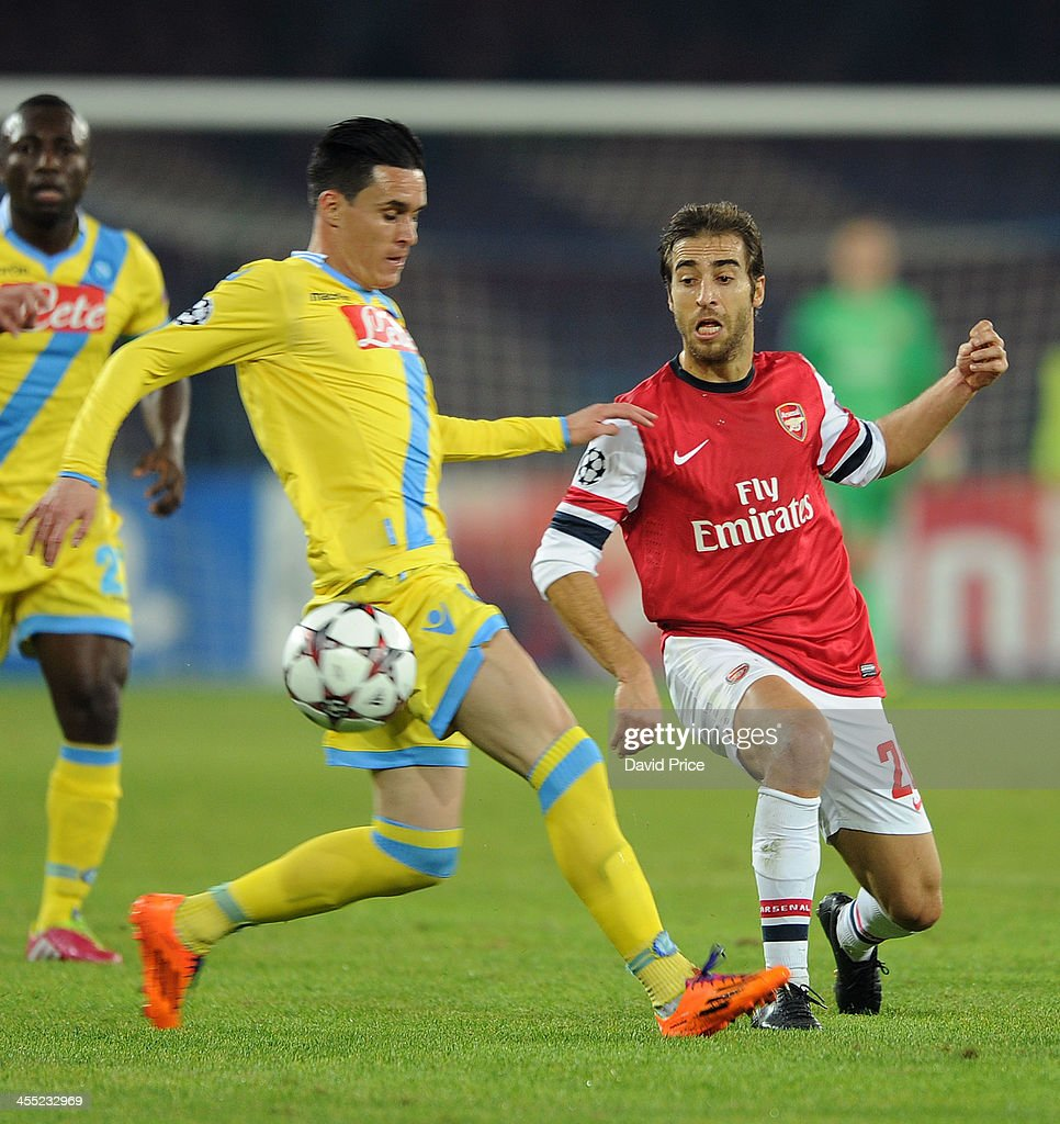 Mathieu Flamini of Arsenal passes the ball under pressure from Jose Callejon of Napoli during the match Napoli against Arsenal in the UEFA Champions...
