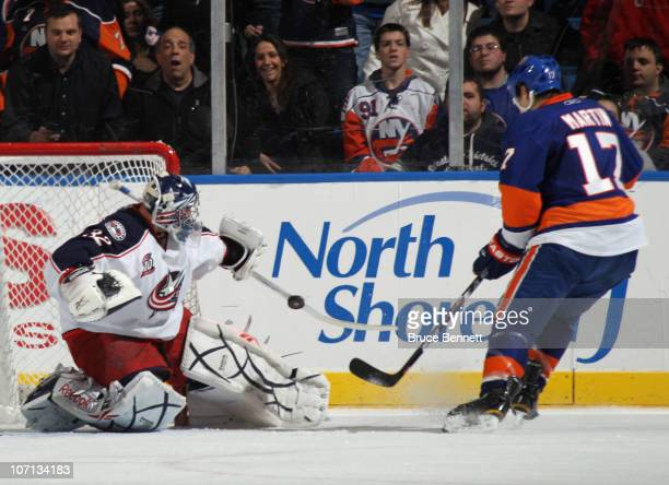Mathieu Garon of the Columbus Blue Jackets makes the stop on Matt Martin of the New York Islanders at the Nassau Coliseum on November 24 2010 in...