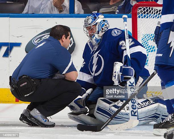Mathieu Garon of the Tampa Bay Lightning is checked by the team athletic trainer during the first period against the Ottawa Senators at the Tampa Bay...