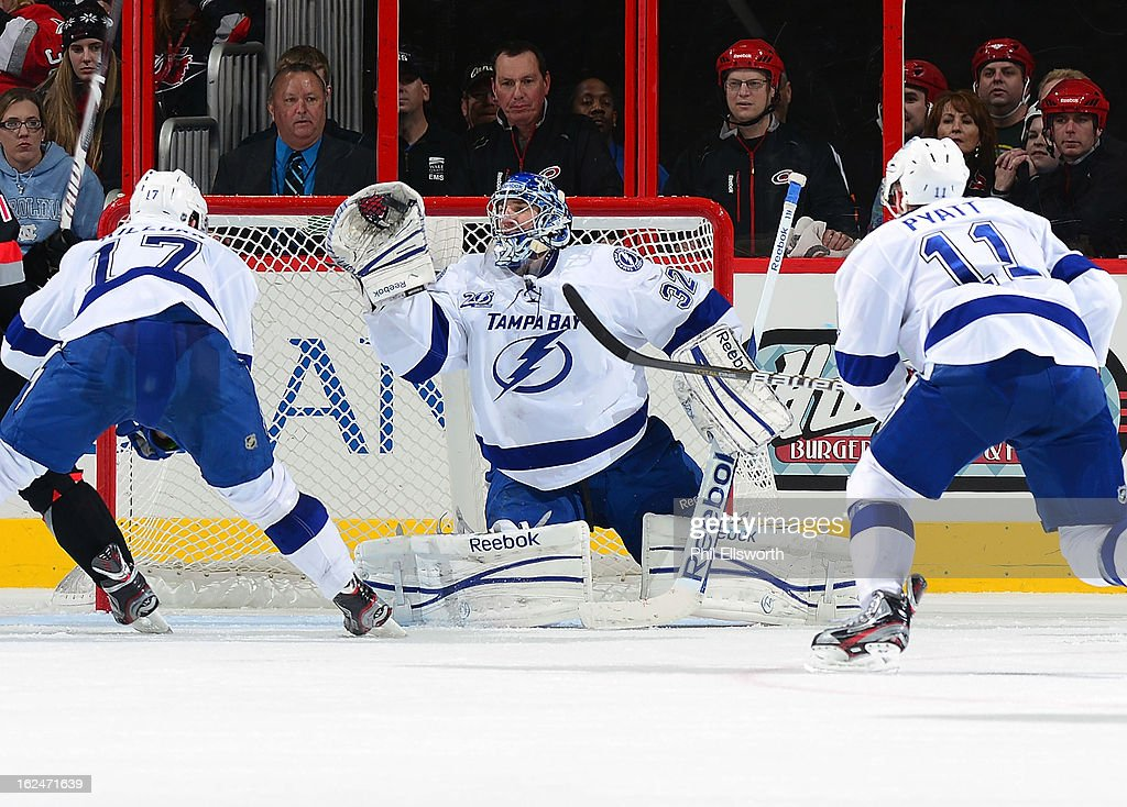 <a gi-track='captionPersonalityLinkClicked' href=/galleries/search?phrase=Mathieu+Garon&family=editorial&specificpeople=206119 ng-click='$event.stopPropagation()'>Mathieu Garon</a> #32 of the Tampa Bay Lightning makes a glove save on a Carolina Hurricanes shot as Alexander Killorn #17 and Tom Pyatt #11 approach the crease during an NHL game on February 23, 2013 at PNC Arena in Raleigh, North Carolina.