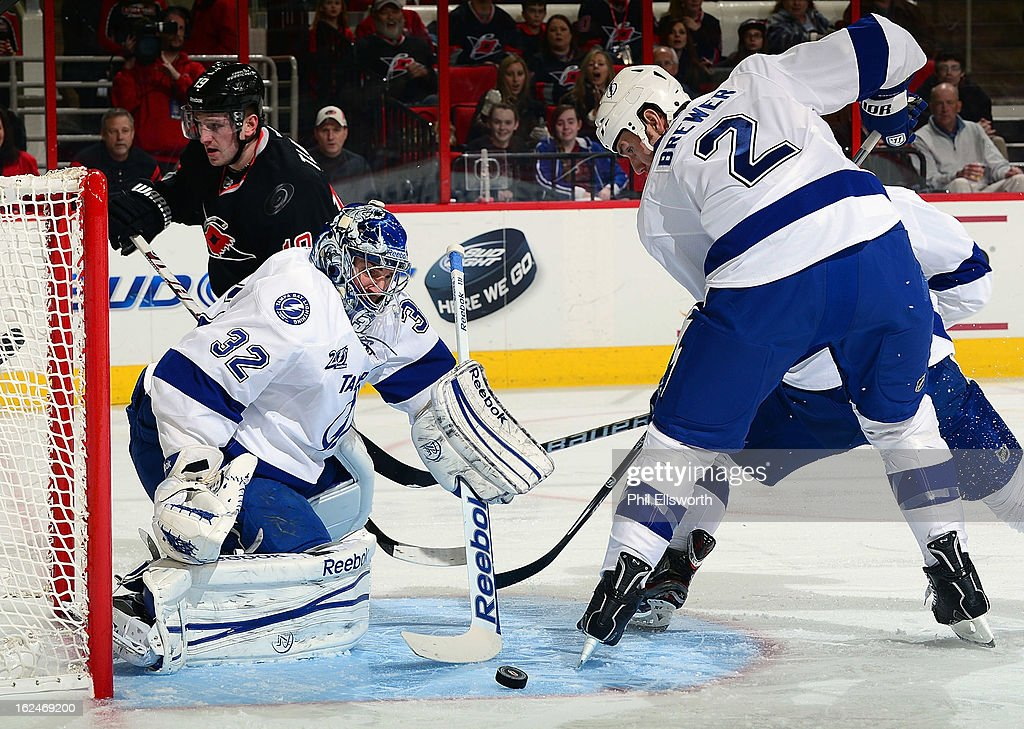 <a gi-track='captionPersonalityLinkClicked' href=/galleries/search?phrase=Mathieu+Garon&family=editorial&specificpeople=206119 ng-click='$event.stopPropagation()'>Mathieu Garon</a> #32 of the Tampa Bay Lightning slides across the crease to block a Carolina Hurricanes shot behind defenseman Eric Brewer #2 during an NHL game on February 23, 2013 at PNC Arena in Raleigh, North Carolina.