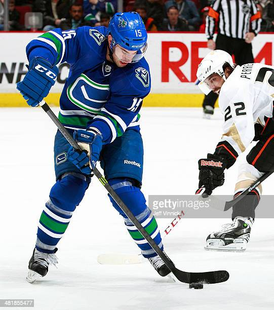 Mathieu Perreault of the Anaheim Ducks tries to check Brad Richardson of the Vancouver Canucks as he skates up ice with the puck during their NHL...