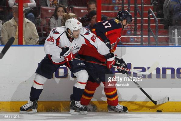 Mathieu Perreault of the Washington Capitals battles along the boards for control of the puck with Filip Kuba of the Florida Panthers at the BBT...