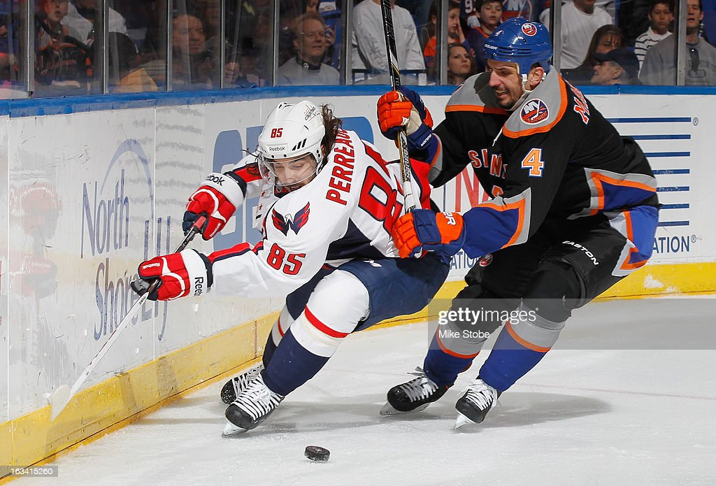 Mathieu Perreault #85 of the Washington Capitals pursues the puck against Radek Martinek #4 of the New York Islanders at Nassau Veterans Memorial Coliseum on March 9, 2013 in Uniondale, New York.