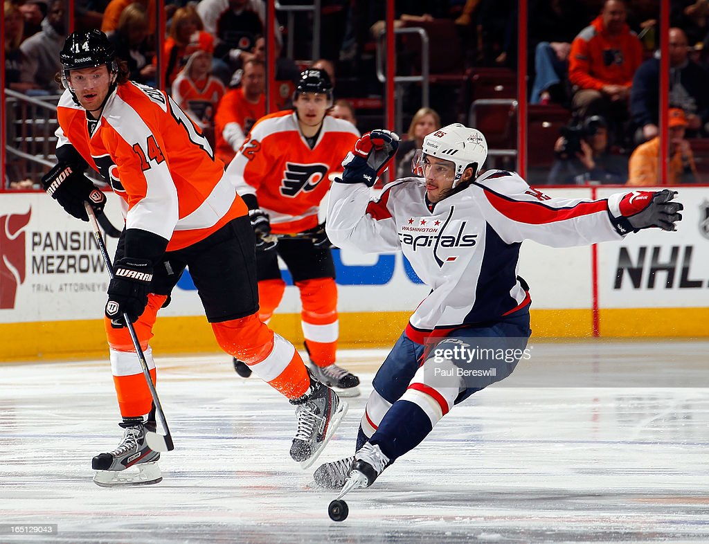 <a gi-track='captionPersonalityLinkClicked' href=/galleries/search?phrase=Mathieu+Perreault&family=editorial&specificpeople=776813 ng-click='$event.stopPropagation()'>Mathieu Perreault</a> #85 of the Washington Capitals tries to block a pass with his skate by <a gi-track='captionPersonalityLinkClicked' href=/galleries/search?phrase=Sean+Couturier&family=editorial&specificpeople=5663953 ng-click='$event.stopPropagation()'>Sean Couturier</a> #14 of the Philadelphia Flyers in the second period of an NHL hockey game at Wells Fargo Center on March 31, 2013 in Philadelphia, Pennsylvania. Flyers won 5-4 in overtime.