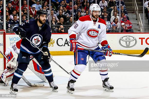 Mathieu Perreault of the Winnipeg Jets and Andrei Markov of the Montreal Canadiens keep an eye on the play during second period action at the MTS...