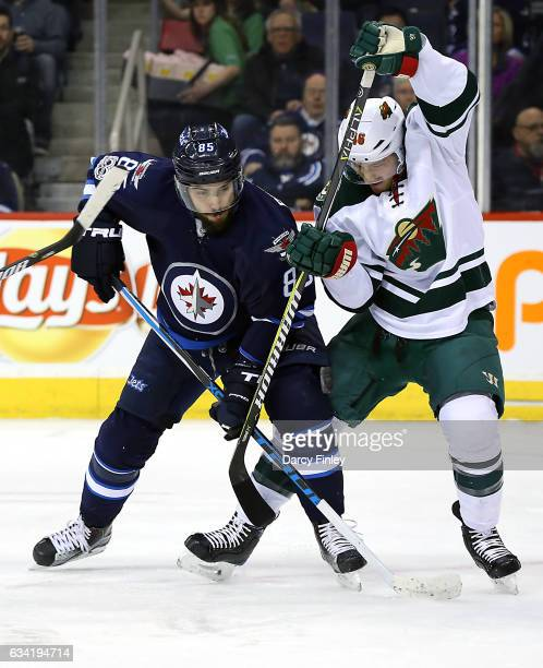 Mathieu Perreault of the Winnipeg Jets battles Jared Spurgeon of the Minnesota Wild for position during first period action at the MTS Centre on...