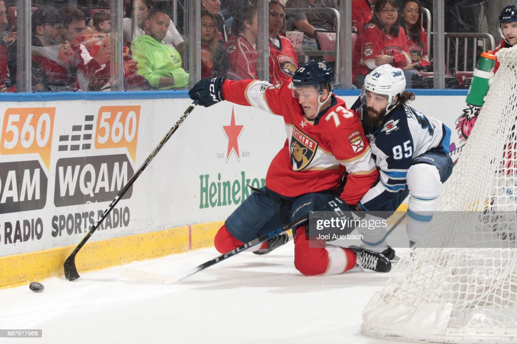 Mathieu Perreault #85 of the Winnipeg Jets defends against Dryden Hunt #73 of the Florida Panthers as he circles behind the net with the puck during first period action at the BB&T Center on December 7, 2017 in Sunrise, Florida.