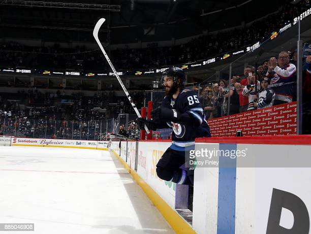 Mathieu Perreault of the Winnipeg Jets salutes the fans after receiving second star honors following a 50 victory over the Ottawa Senators at the...