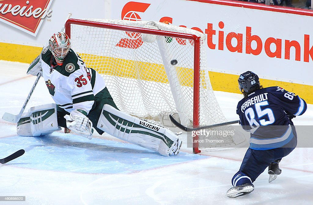 Mathieu Perreault of the Winnipeg Jets shoots the puck over the pad of goaltender Darcy Kuemper of the Minnesota Wild for a second period goal on...