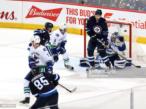 Mathieu Perreault of the Winnipeg Jets watches as his shot gets past a screened Ryan Miller of the Vancouver Canucks for a second period goal at the...