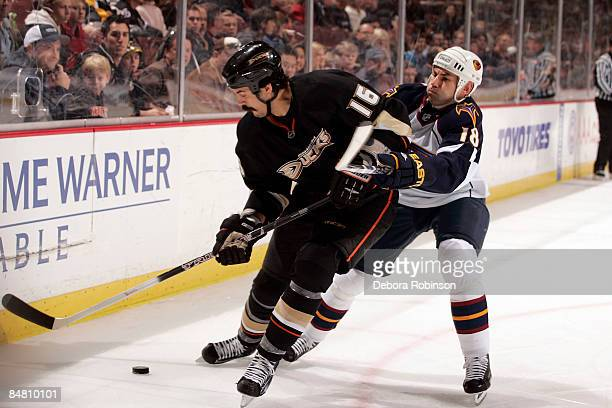 Mathieu Schneider of the Atlanta Thrashers reaches around George Parros of the Anaheim Ducks during the game on February 15 2009 at Honda Center in...