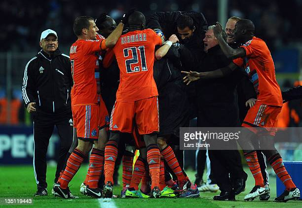 Mathieu Valbuena of Marseille celebrates with head coach Didier Deschamps and team mates after scoring the winning goal during the UEFA Champions...