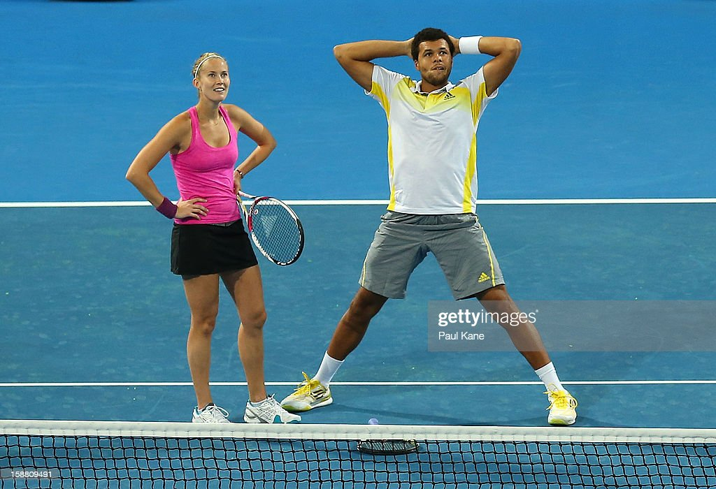 Mathilde Johansson and Jo-Wilfried Tsonga and of France wait for a review in their mixed doubles match against Fernando Verdasco and Anabel Medina Garrigues of Spain during day two of the Hopman Cup at Perth Arena on December 30, 2012 in Perth, Australia.