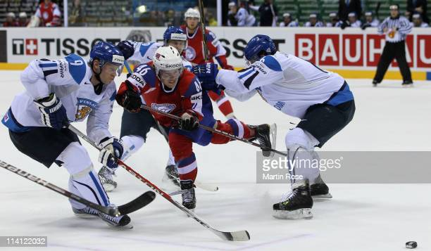Mathis Olimb of Norway is attacked by Mikko Koivu and Topi Jaakola of Finland during the IIHF World Championship quarter final match between Finland...
