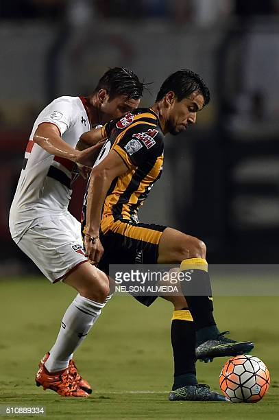 Matias Alonso of Bolivia's The Strongest vies for the ball with Mena of Brazils Sao Paulo during their 2016 Copa Libertadores football match held at...