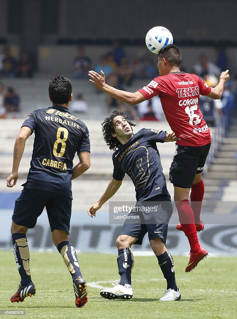 Matias Britos and David Cabrera of Pumas UNAM figths for the ball with Joe Corona of Xolos of Tijuana during a match between Pumas UNAM and Xolos Tijuana as part of 6th round Apertura 2014 Liga MX at Olimpic Stadium on August 24, 2014 in Mexico City, Mexico.