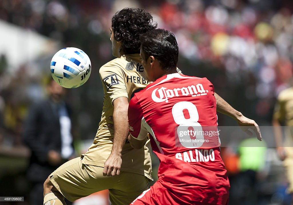 Matias Britos (L) of Pumas compete for the ball with Aaron Galindo of Toluca during a match between Toluca and Pumas as part of 4th round Apertura 2014 Liga MX at Nemesio Diez Stadium on August 3, 2014 in Toluca, Mexico.
