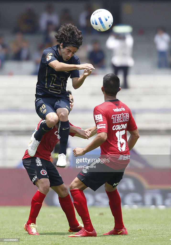 Matias Britos of Pumas UNAM jumps for the ball with <a gi-track='captionPersonalityLinkClicked' href=/galleries/search?phrase=Joe+Corona&family=editorial&specificpeople=8282654 ng-click='$event.stopPropagation()'>Joe Corona</a> of Xolos Tijuana during a match between Pumas UNAM and Xolos Tijuana as part of 6th round Apertura 2014 Liga MX at Olimpic Stadium on August 24, 2014 in Mexico City, Mexico.