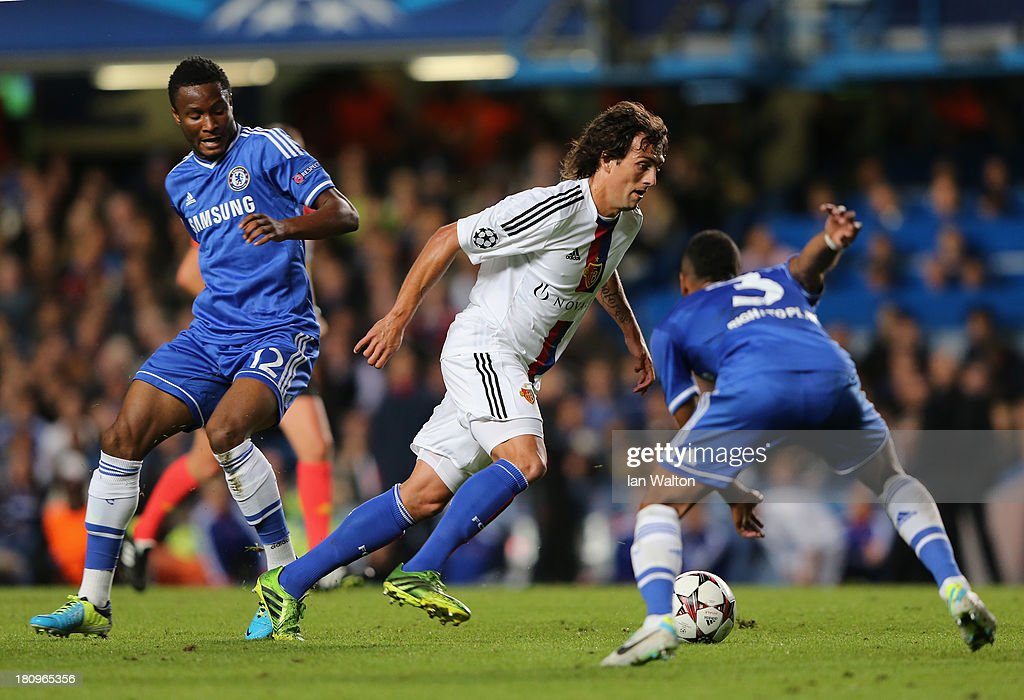 Matias Emilio Delgado of FC Basel is closed down by John Obi Mikel and Ashley Cole of Chelsea during the UEFA Champions League Group E Match between Chelsea and FC Basel at Stamford Bridge on September 18, 2013 in London, England.