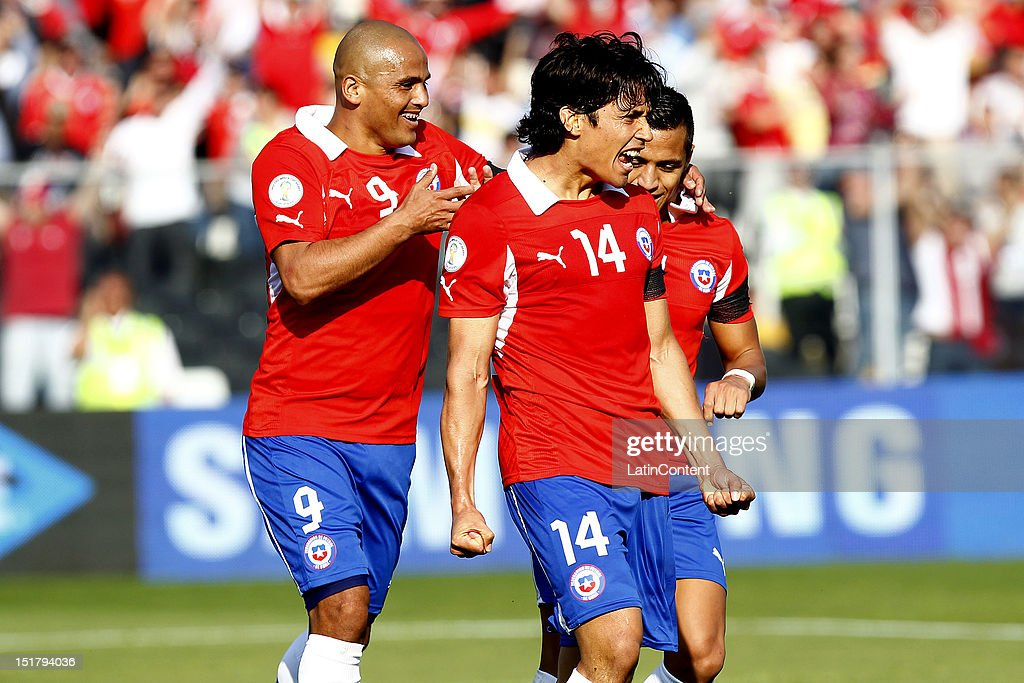 Matias Fernandez Humerto Suazo and Alesis Sanchez of Chile celebrate a goal during a match between Chile and Colombia as part of the South American...