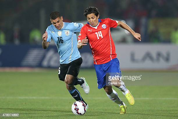 Matias Fernandez of Chile fights for the ball with Maximiliano Pereira of Uruguay during the 2015 Copa America Chile quarter final match between...