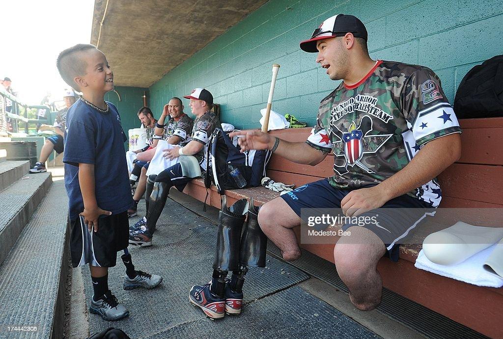 Matias Ferreira jokes around with batboy Ethan Perez before a Wounded Warriors softball game in Modesto California