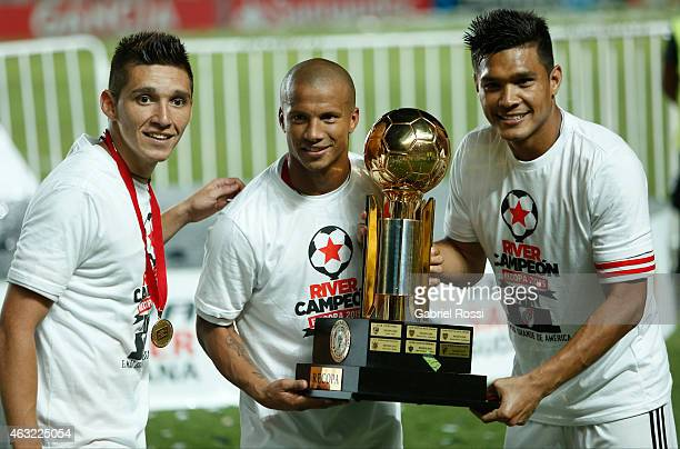 Matias Kranevitter Carlos Sanchez and Teofilo Gutierrez of River Plate pose for a photo with the trophy after winning a second leg match between San...