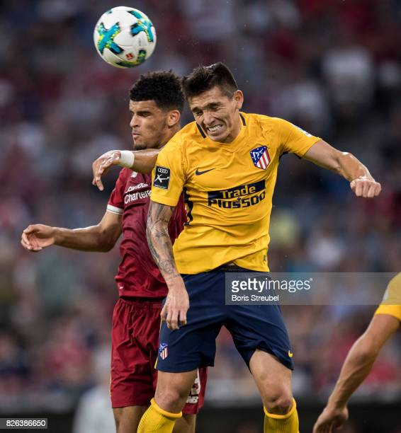 Matias Kranevitter of Atletico Madrid jumps for a header with Dominic Solanke of Liverpool FC during the Audi Cup 2017 match between Liverpool FC and...