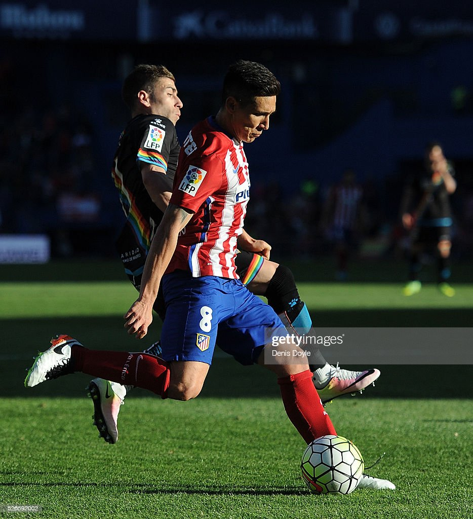 Matias Kranevitter of Club Atletico de Madrid gets past Adrian Embarba of Rayo Vallecano during the La Liga match between Club Atletico de Madrid and Rayo Vallecano at Vicente Calderon Stadium on April 30, 2016 in Madrid, Spain.